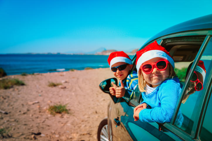 Children in a car wearing Santa hats